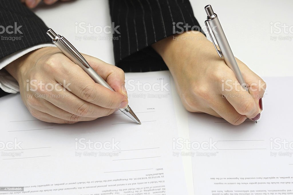 man and woman signing document or prenup stock photo
