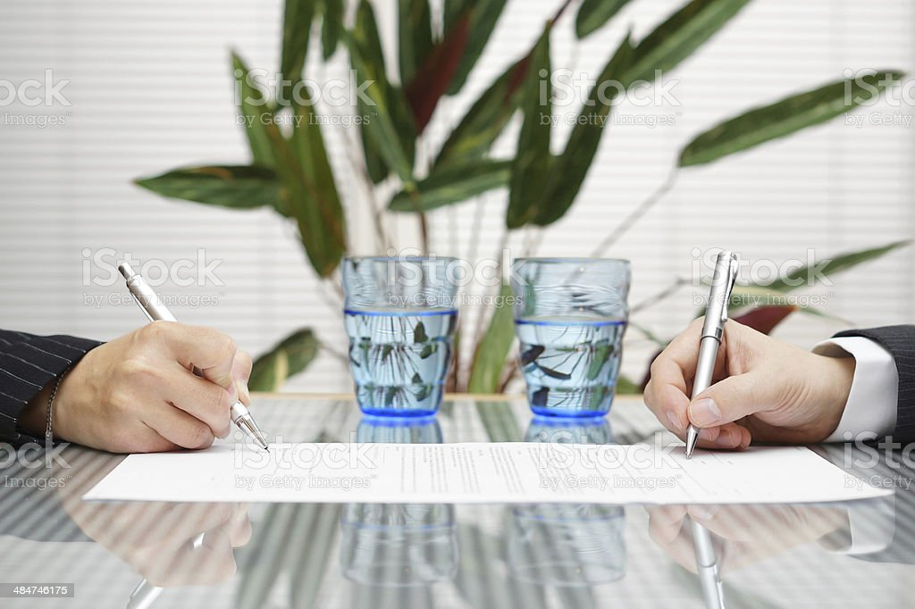 man and woman signing document with divorce or prenuptial agreement stock photo