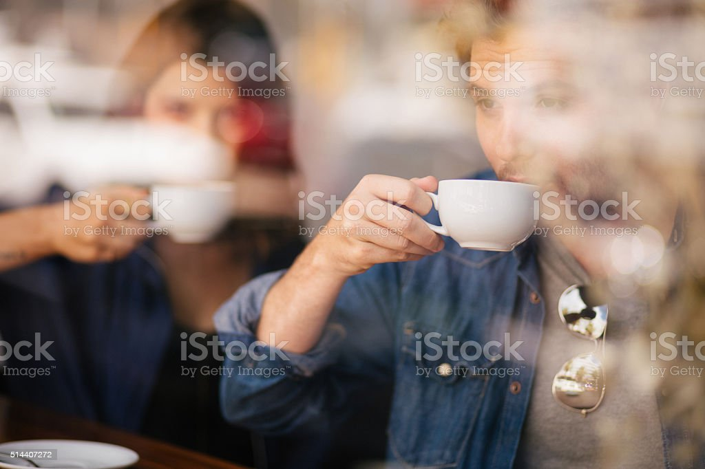 Man and Woman Sipping Their Coffee in Cafe stock photo