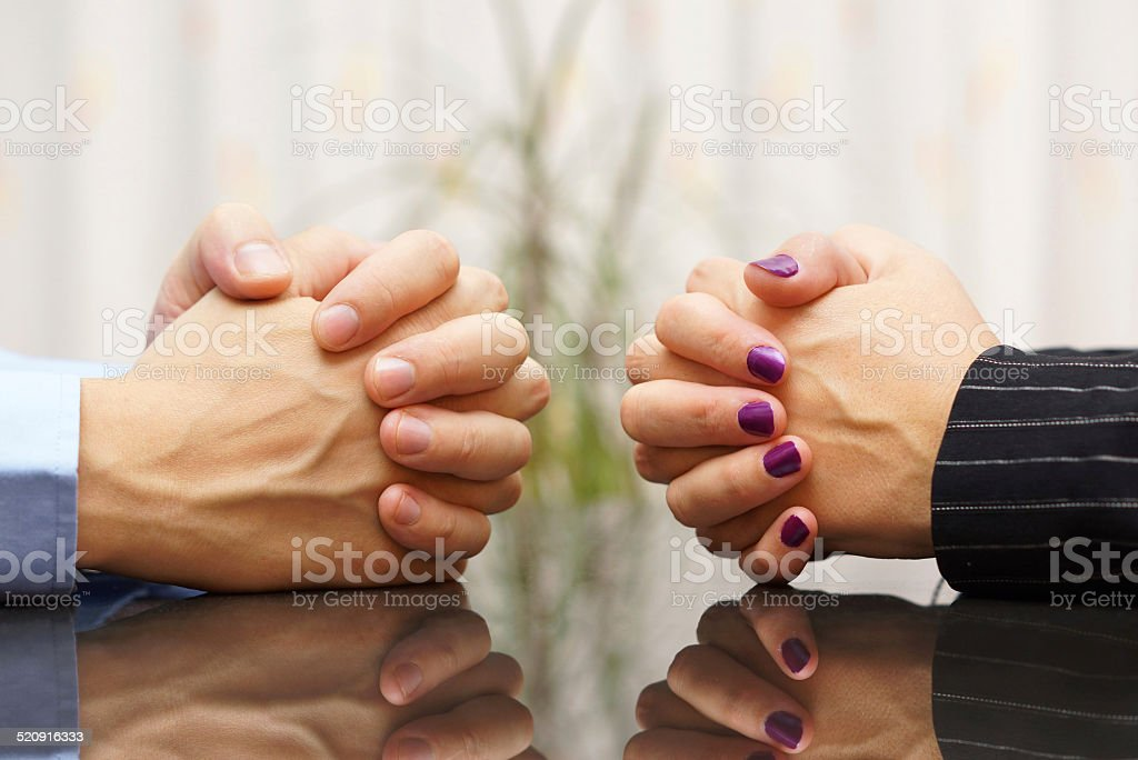 Man and woman sits at a desk with hands clasped. stock photo