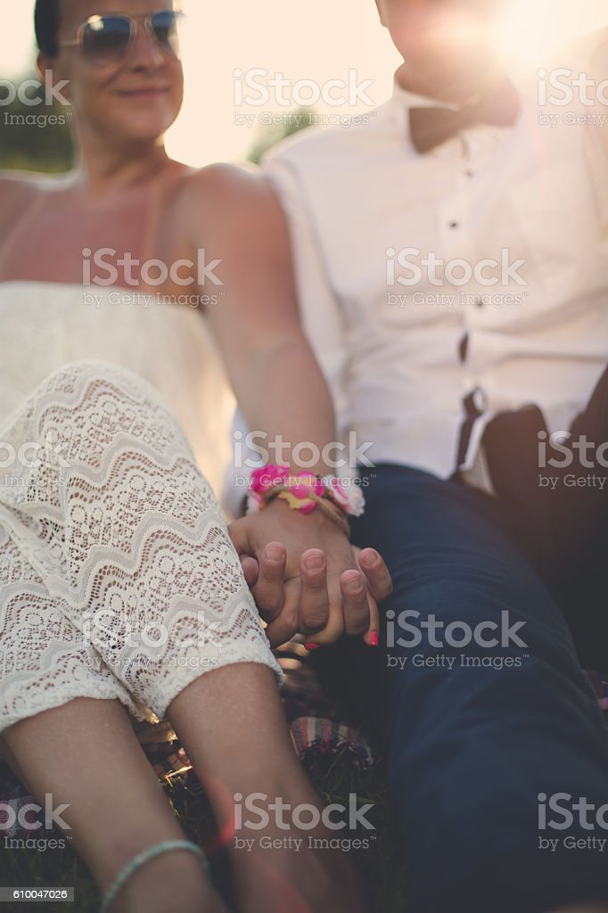 man and woman sitting and holding hands stock photo