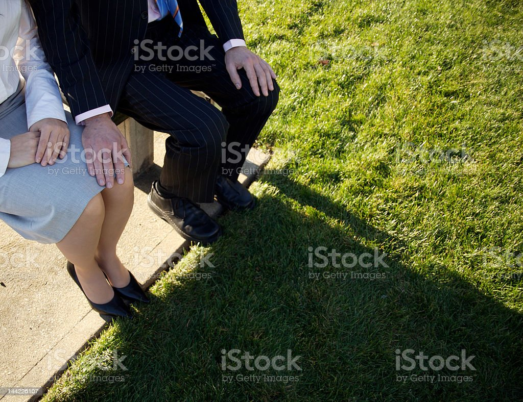 Man and woman sitting on a park bench royalty-free stock photo