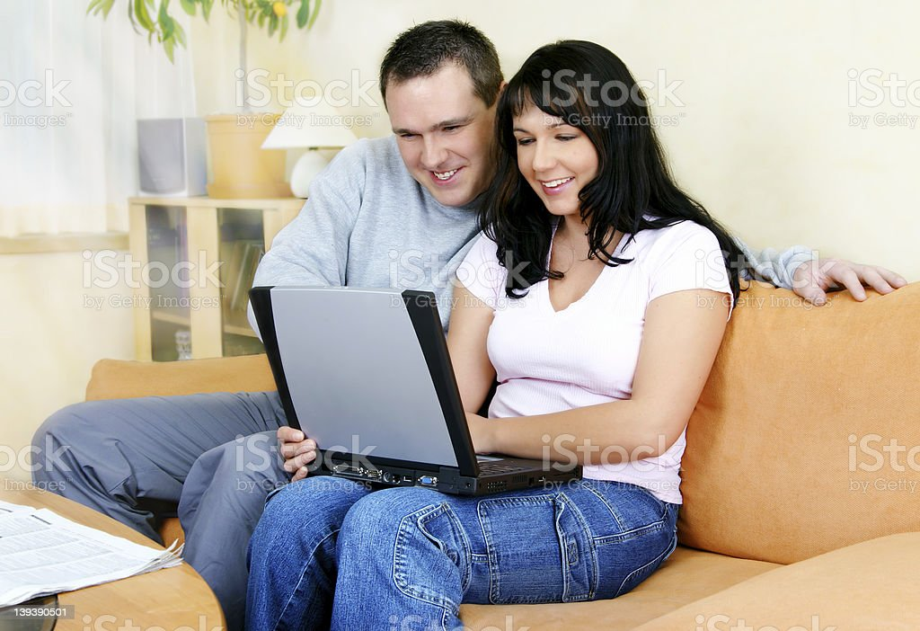 Man and woman sitting on an orange couch looking at a laptop royalty-free stock photo