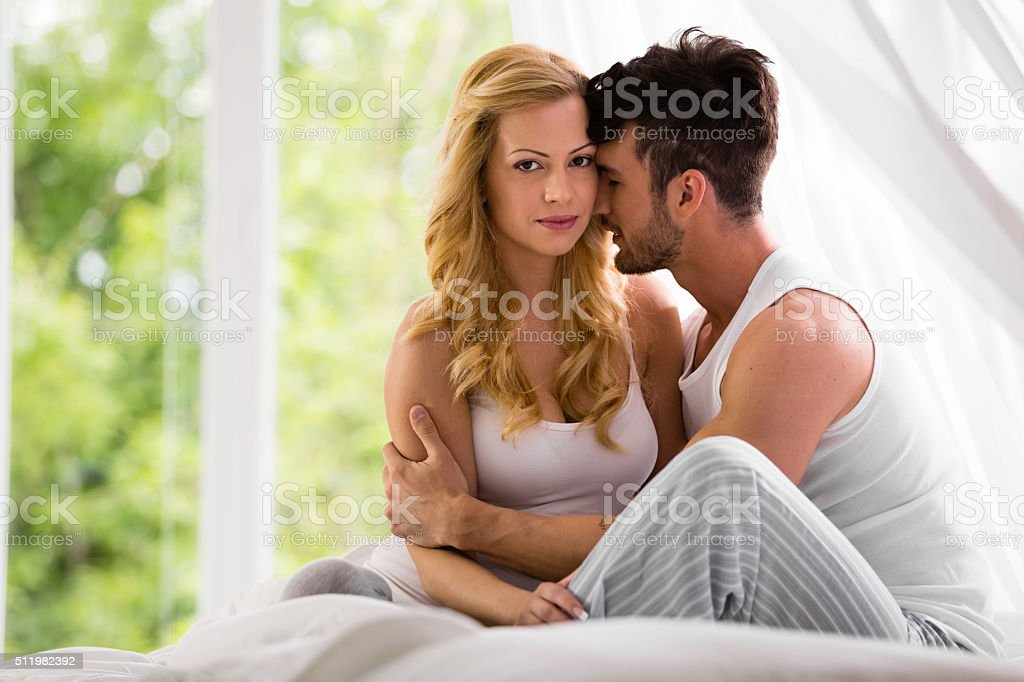 Man and woman sitting on bed in the bedroom stock photo