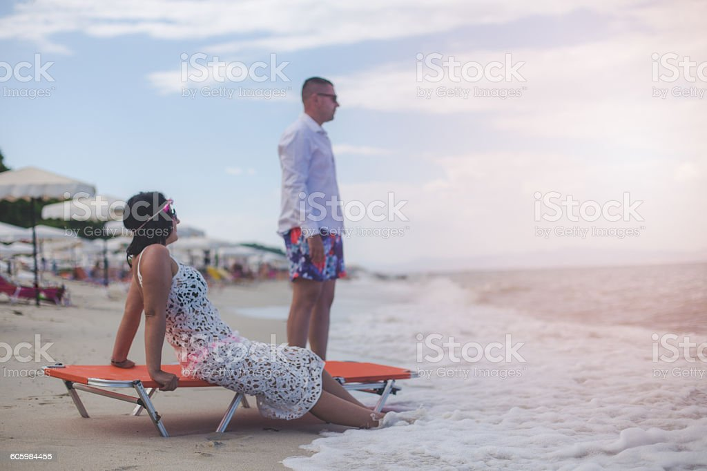 man and woman sitting on the beach stock photo