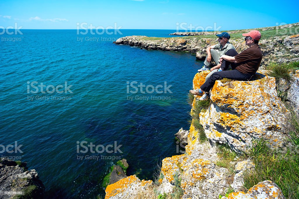 Man and woman sitting on the steep Bank of  sea  . stock photo