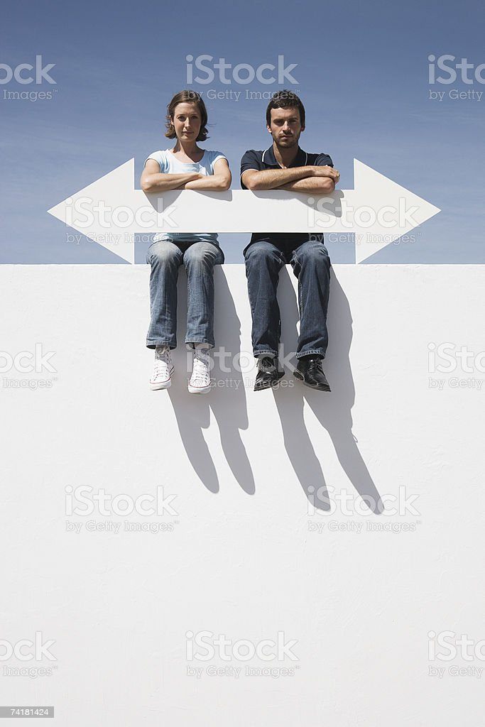 Man and woman sitting on wall outdoors with blank arrow stock photo