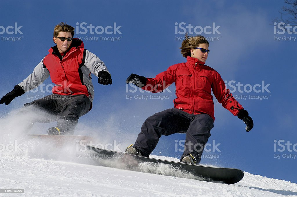 Man and woman snowboarding royalty-free stock photo