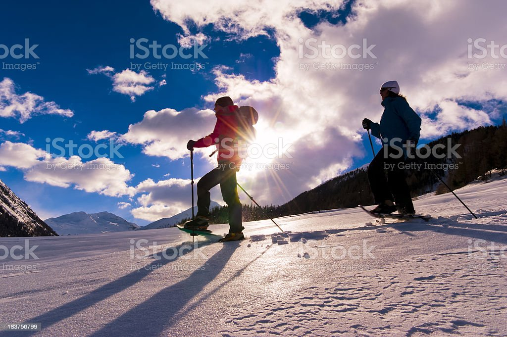 Man and  Woman Snowshoeing stock photo