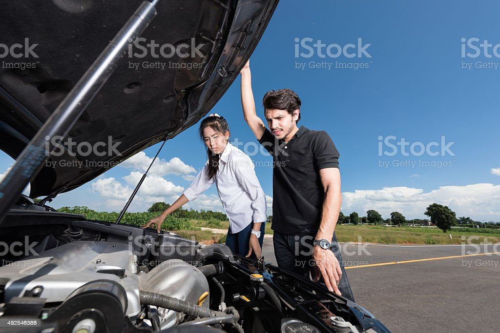 Man and woman stand by the broken car stock photo