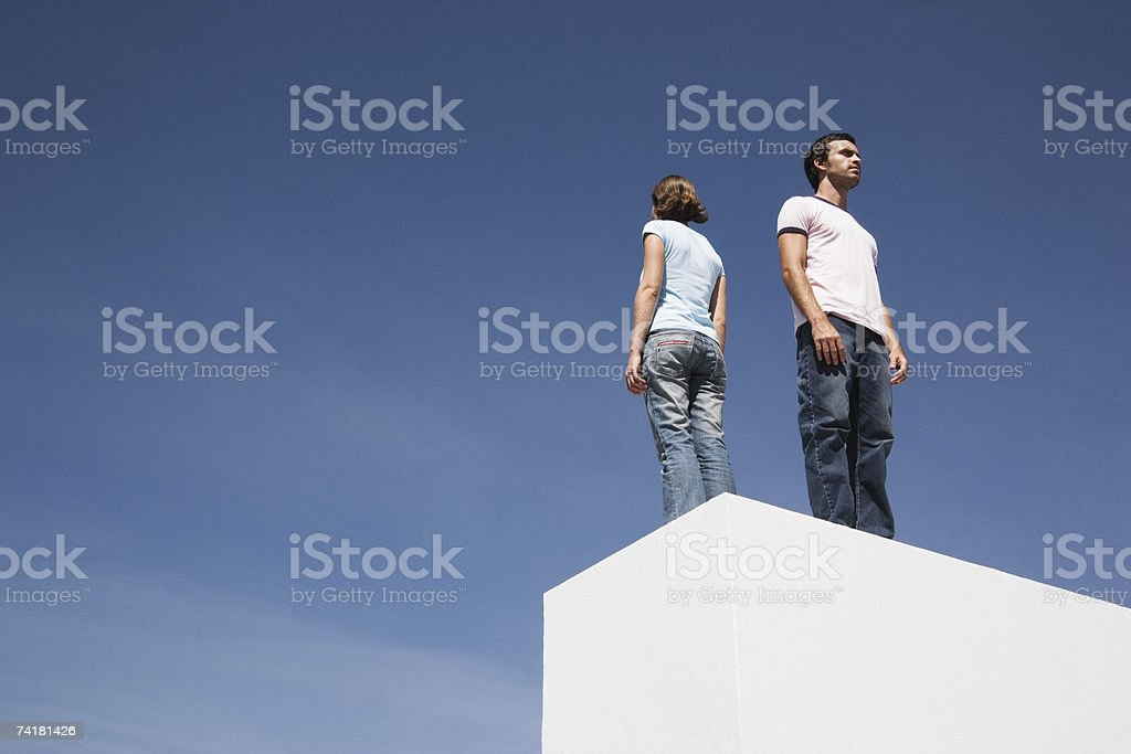 Man and woman standing on box back to back outdoors with blue sky stock photo