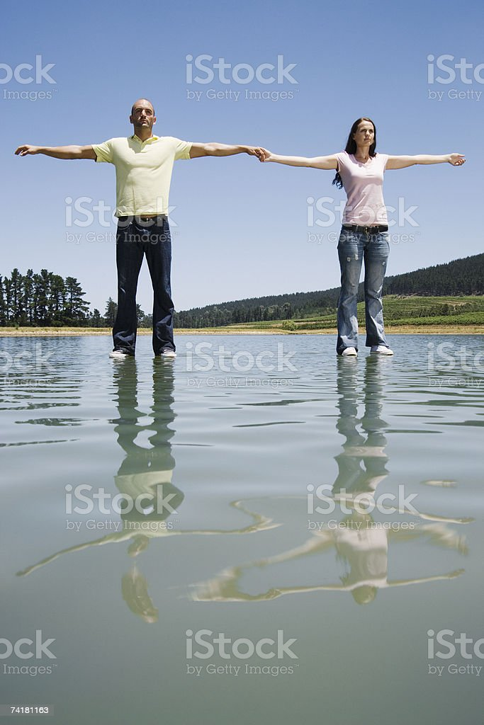 Man and woman standing on water holding hands royalty-free stock photo