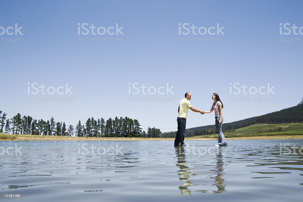 Man and woman standing on water shaking hands royalty-free stock photo