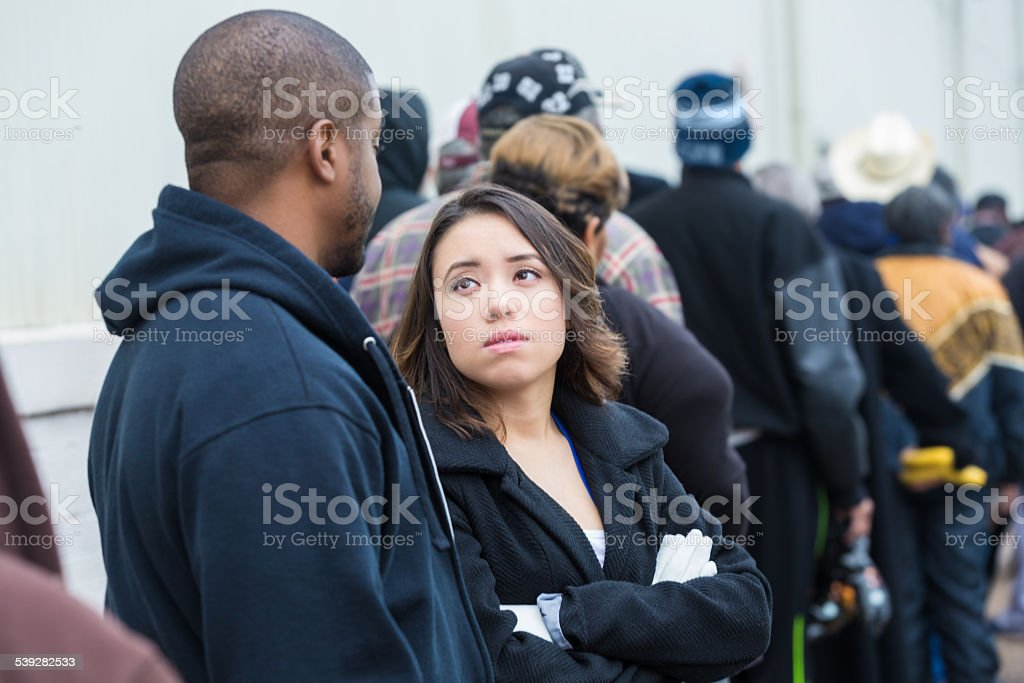 Man and woman standing outside waiting in line stock photo