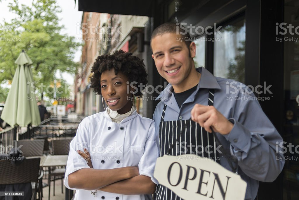 Man and woman standing with an Open sign in his hand royalty-free stock photo