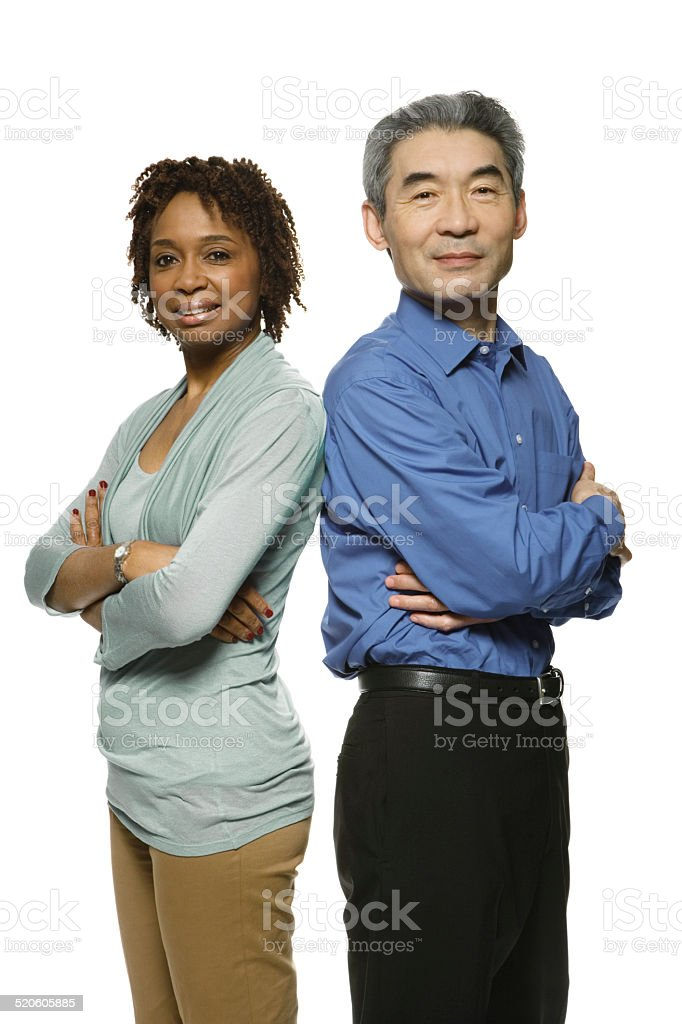 Man and woman standing with arms crossed, smiling stock photo