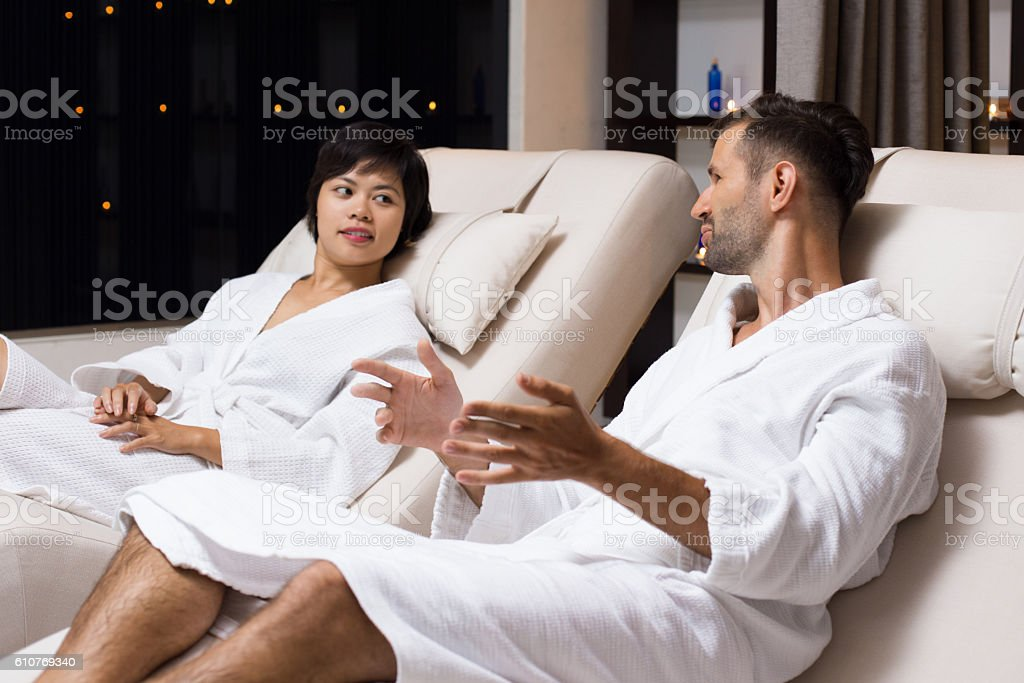 Man and Woman Talking on Loungers in Spa Salon stock photo