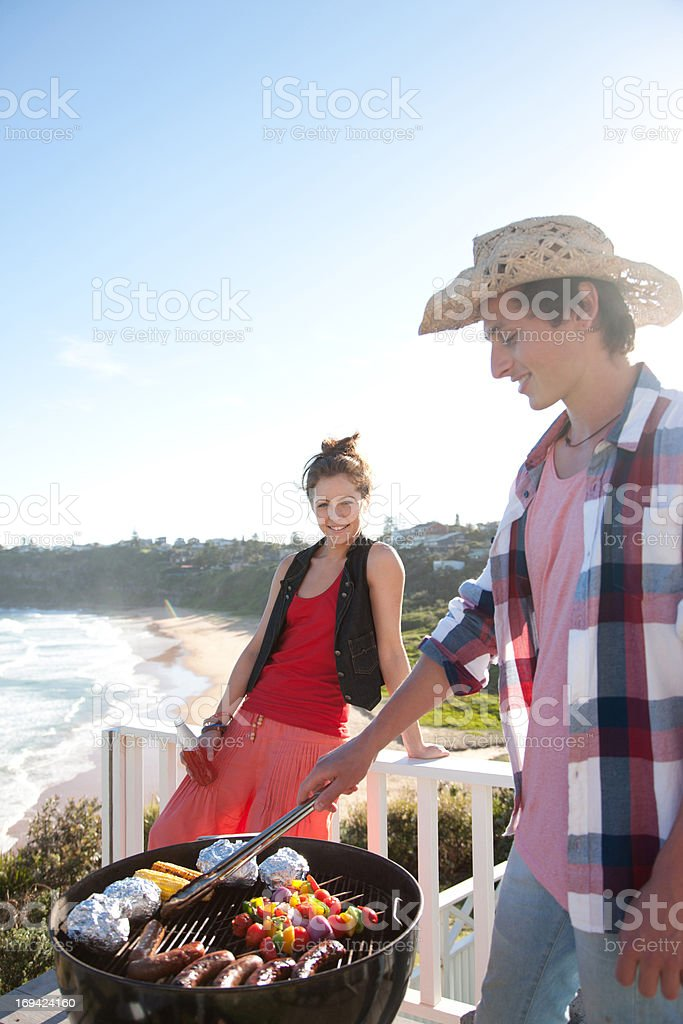 Man and woman tending barbecue with ocean in background stock photo