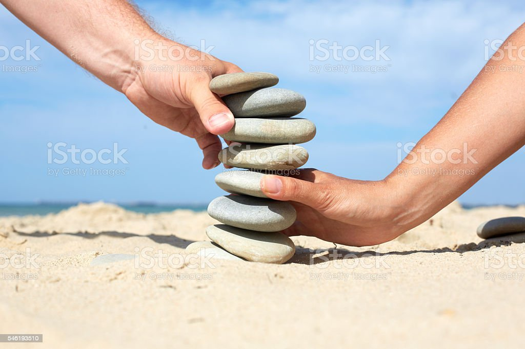 Man and woman together to build  tower made of stones. stock photo