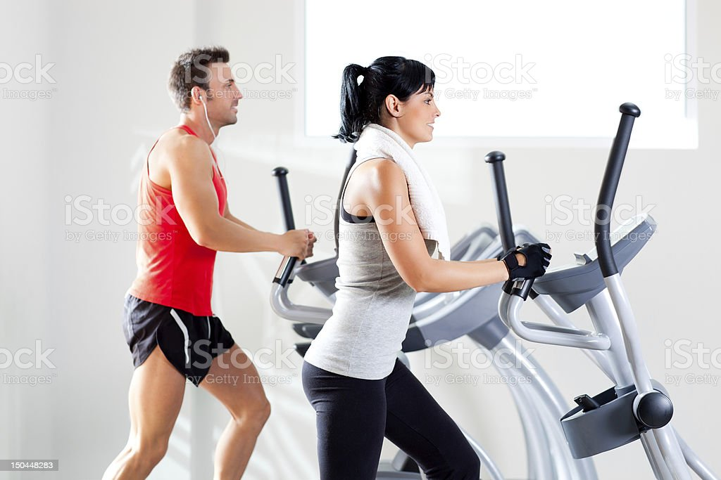 A man and woman using elliptical machines at the gym stock photo