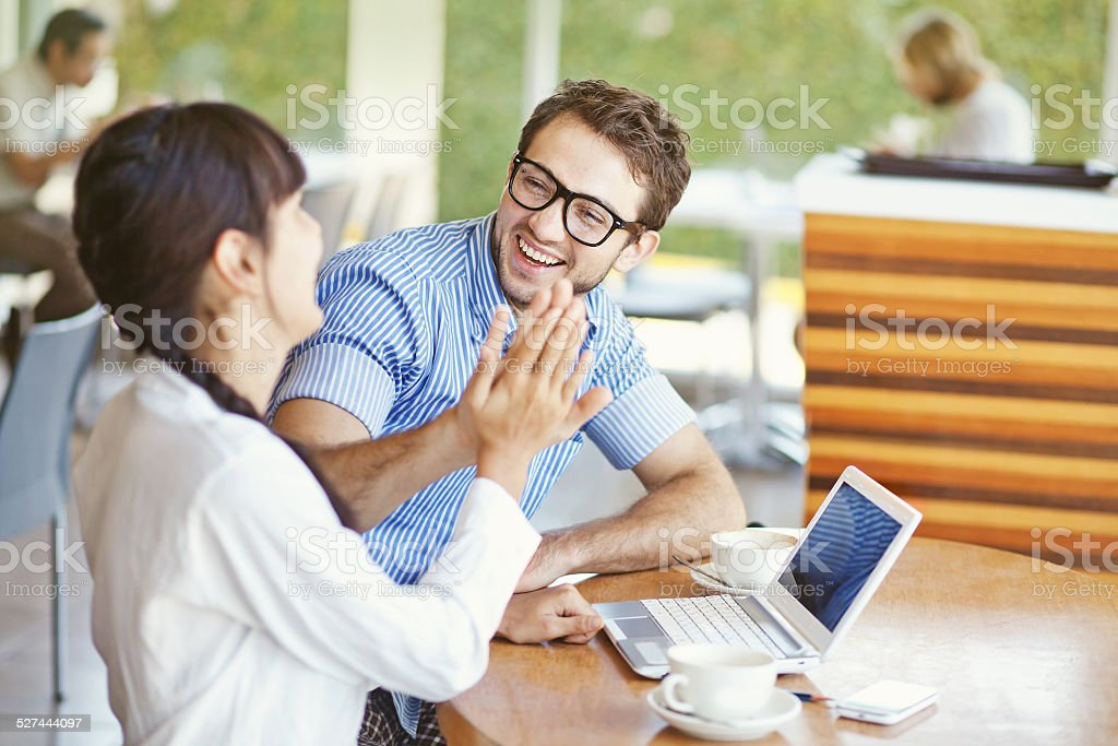 Man and woman using laptop and laughing stock photo