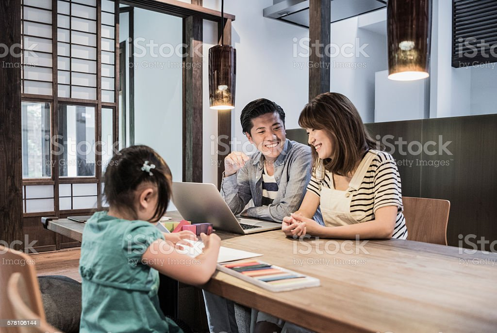 Man and woman using laptop, daughter drawing pictures stock photo