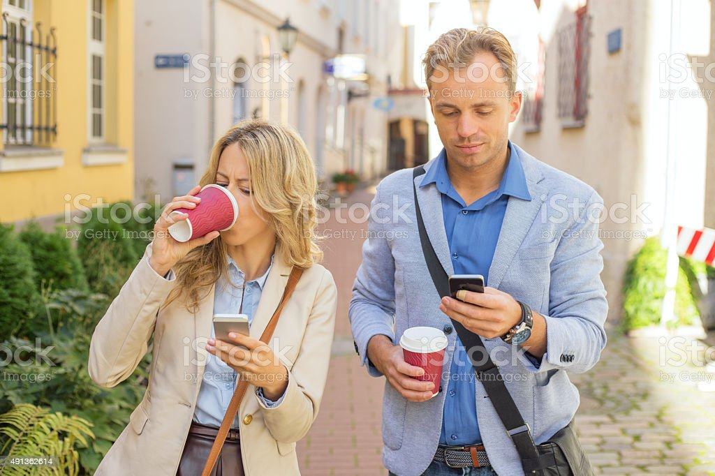 Man and woman using their smartphones stock photo