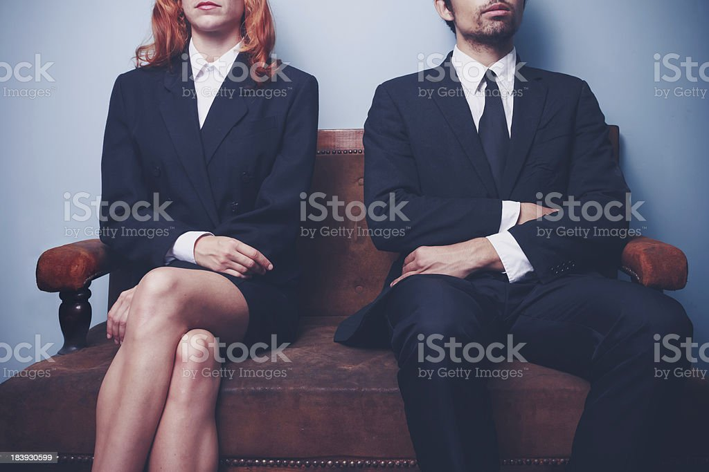 Man and woman waiting on a sofa stock photo