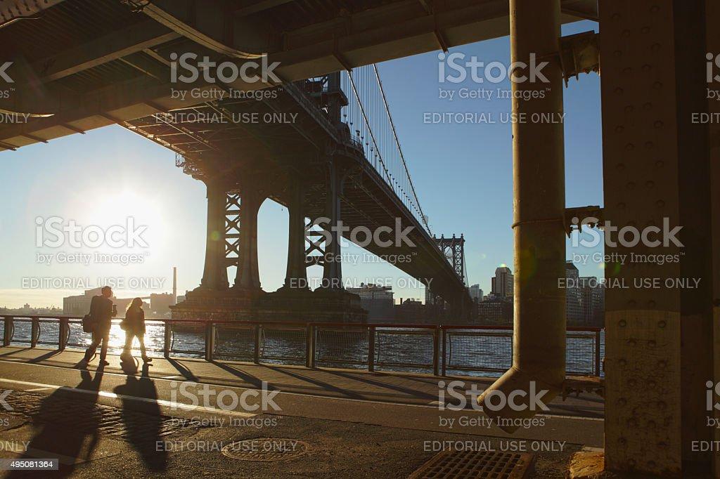 Man and woman walk to work under the Manhattan Bridge stock photo