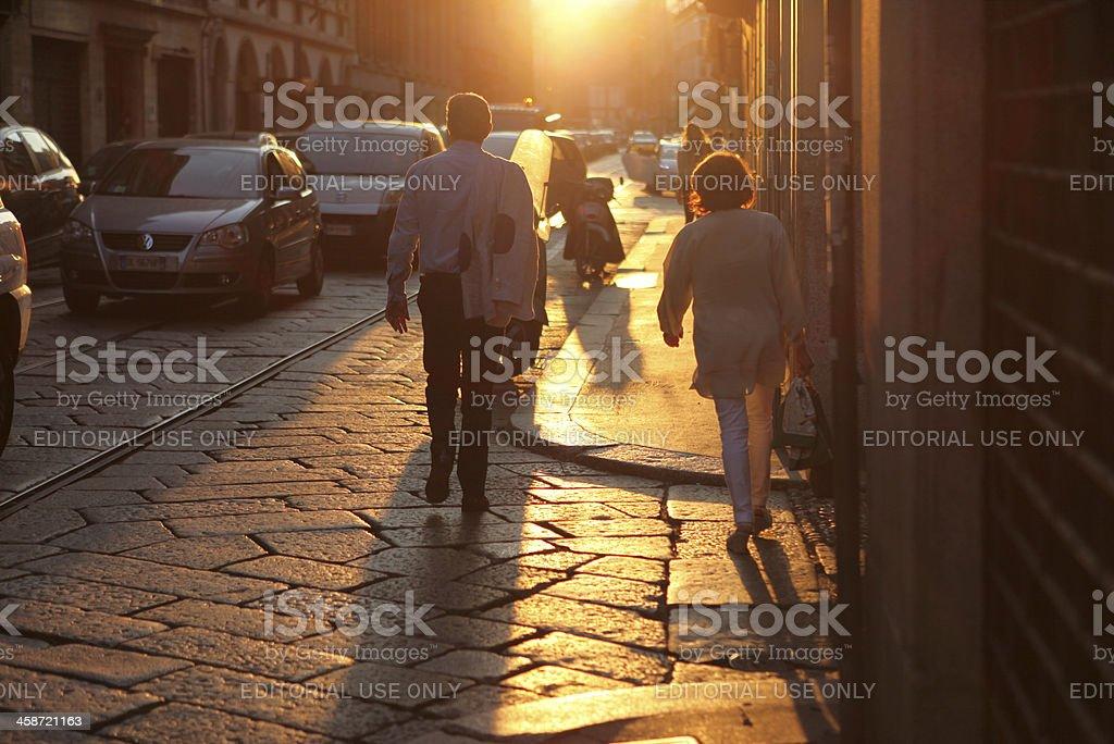 Man and woman walking at sunset in Milan, Italy royalty-free stock photo