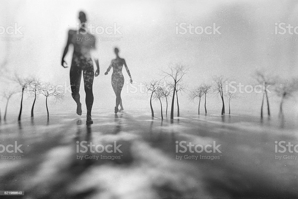 Man and woman walking in fantasy winter landscape stock photo