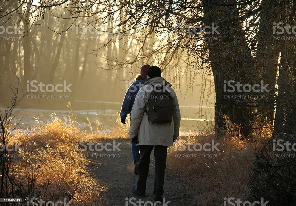 Man and woman walking near the river on winter evening royalty-free stock photo
