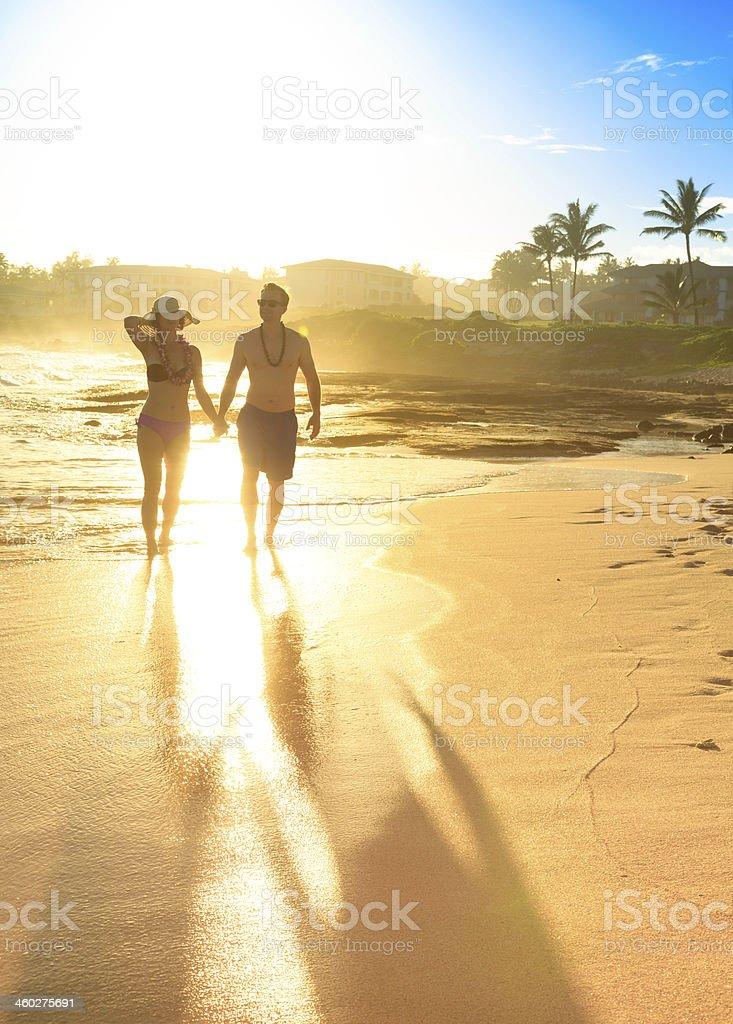 Man and Woman walking on beach in Hawaii stock photo