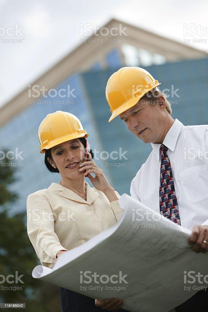 Man and Woman Wearing Hardhats Holding Blueprints royalty-free stock photo