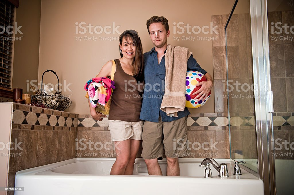 Man and woman with beach gear standing in a bathroom tub stock photo