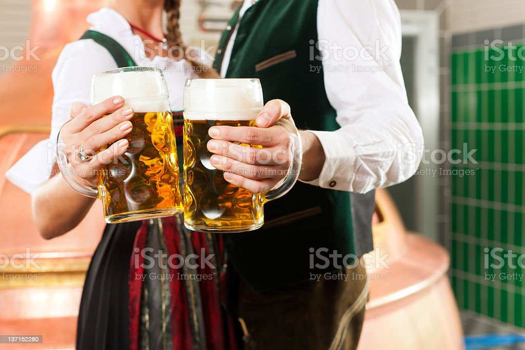 Man and woman with beer glass in brewery stock photo