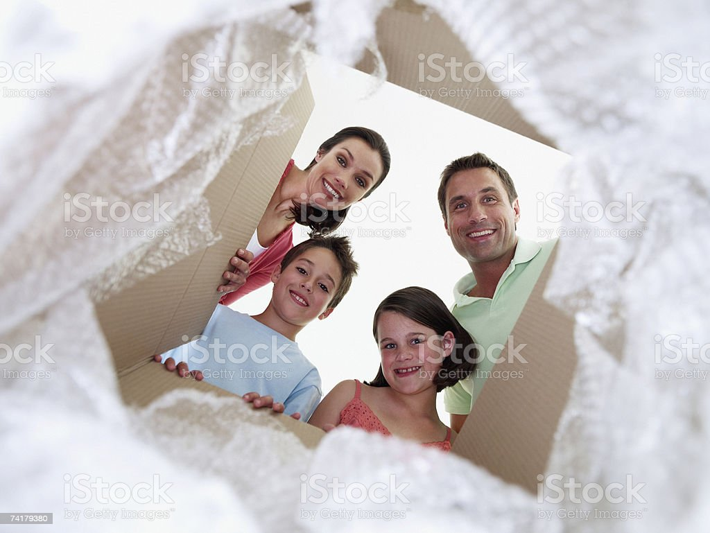 Man and woman with boy and girl looking in cardboard box royalty-free stock photo