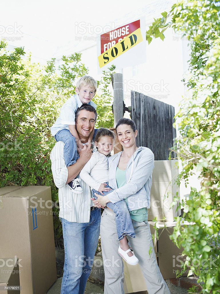 Man and woman with boy and girl outdoors with boxes and sold sign on house stock photo