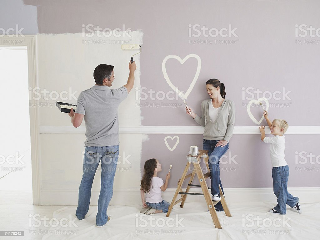 Man and woman with boy and girl painting hearts on wall stock photo