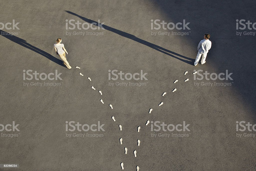 Man and woman with diverging line of footprints royalty-free stock photo