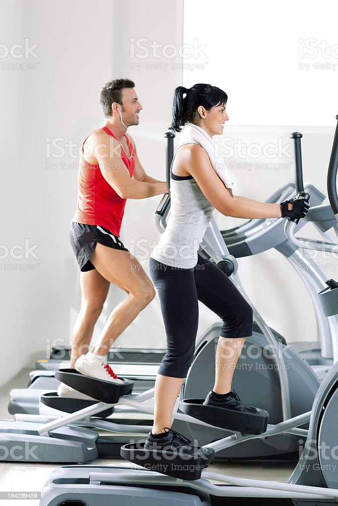man and woman with elliptical cross trainer at gym royalty-free stock photo