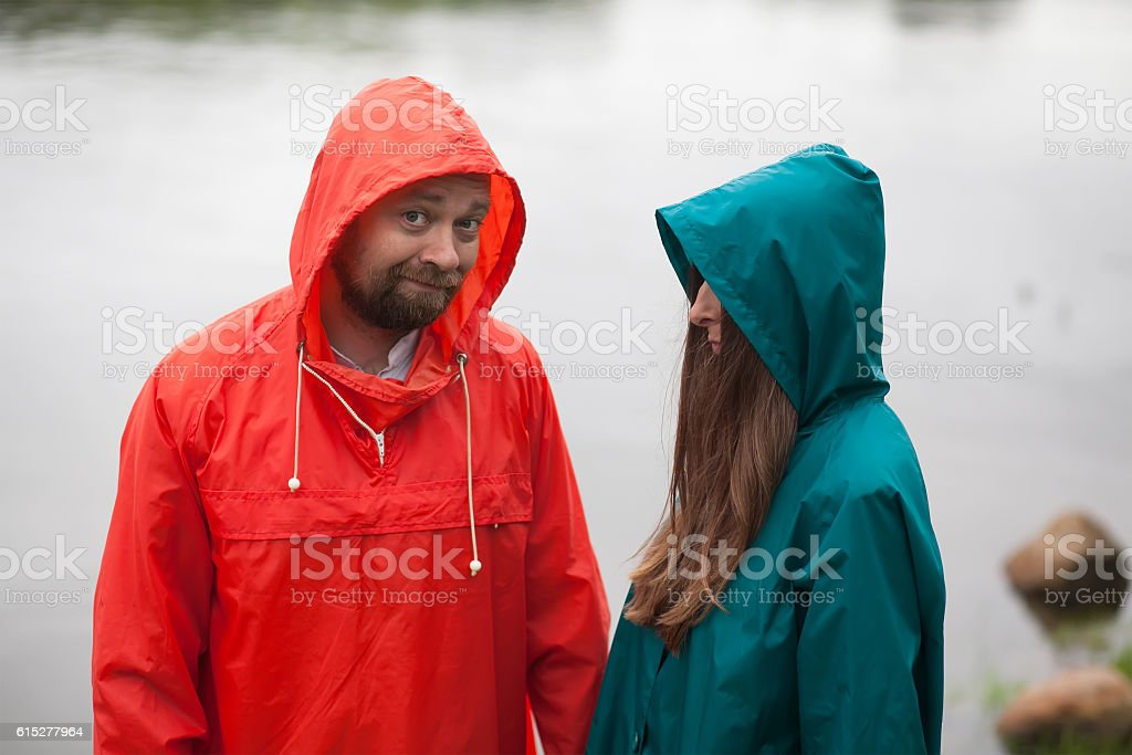 man and woman with flowers, in raincoats royalty-free stock photo