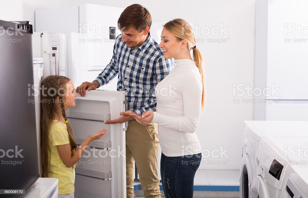 Man and woman with girl buying refrigerator stock photo