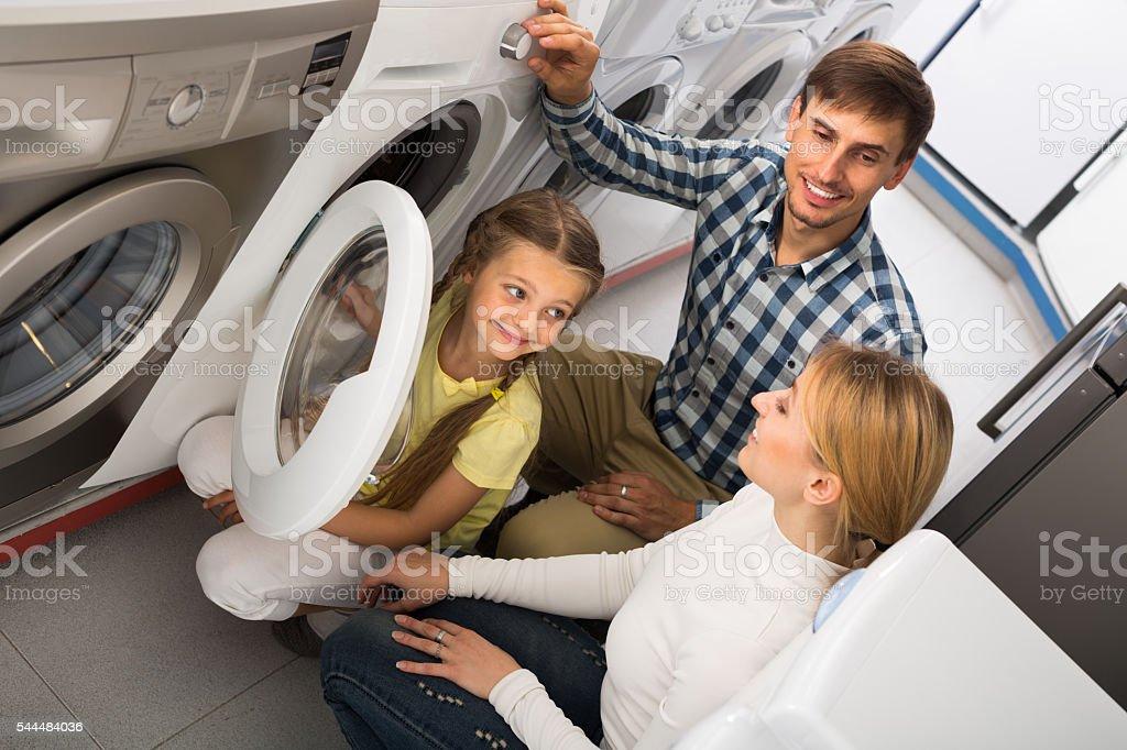 Man and woman with girl buying washing machine stock photo
