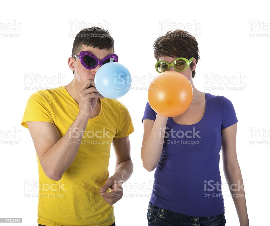 Man and woman with sunglasses blowing balloons royalty-free stock photo