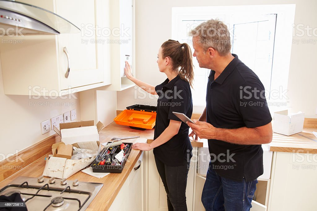 Man and woman working on a new kitchen installation stock photo