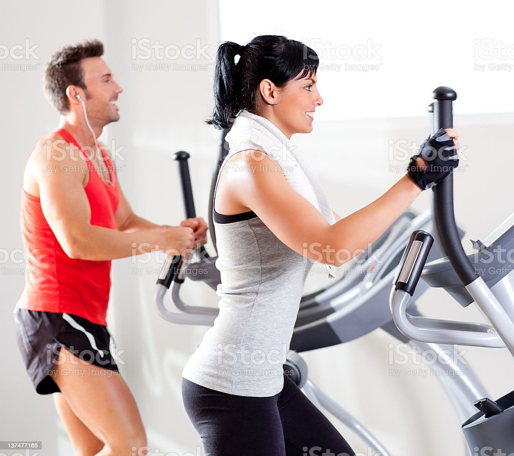A man and woman working out on an elliptical stock photo
