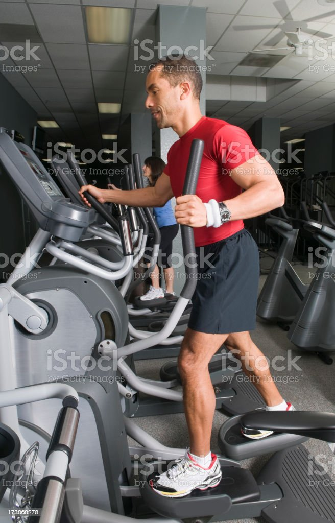 Man and woman workout on an elliptical machine. royalty-free stock photo