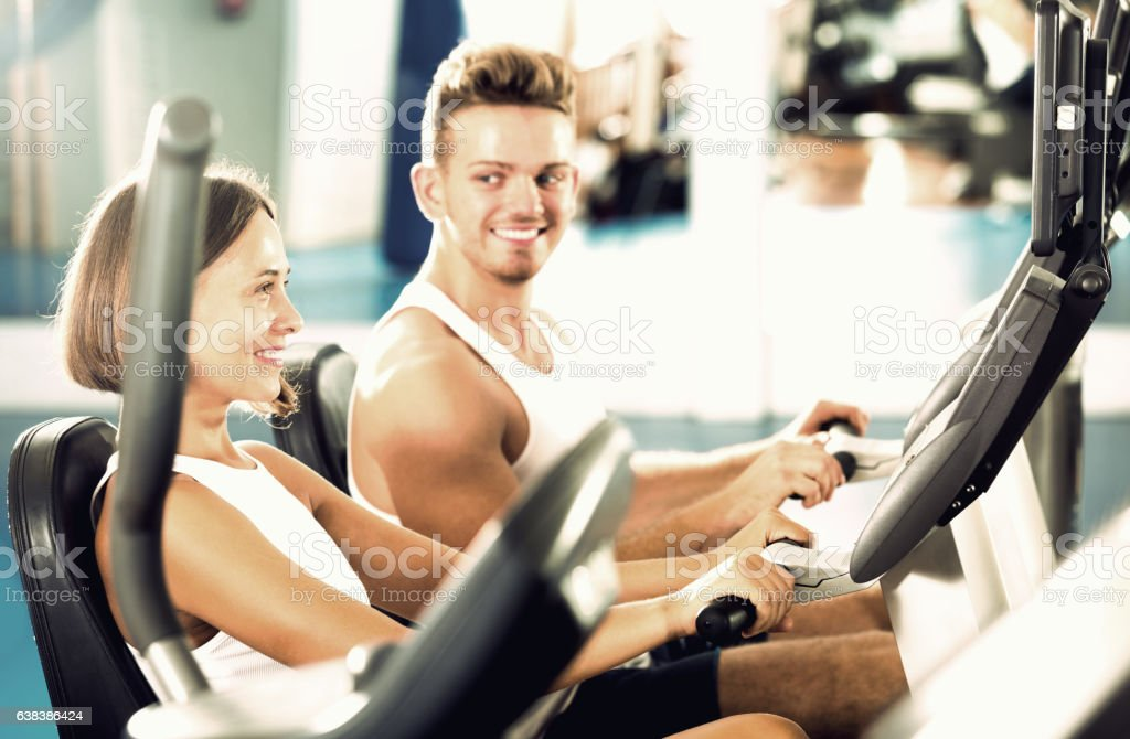 Man and woman workout using cycling cardio machines stock photo