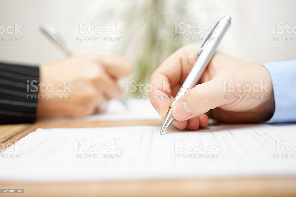 man and woman writing on document stock photo